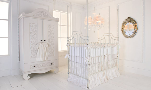 Exclusive elements such as crushed silk, distressed cast iron, carved wood, and crystal make this all white nursery a designer's delight.