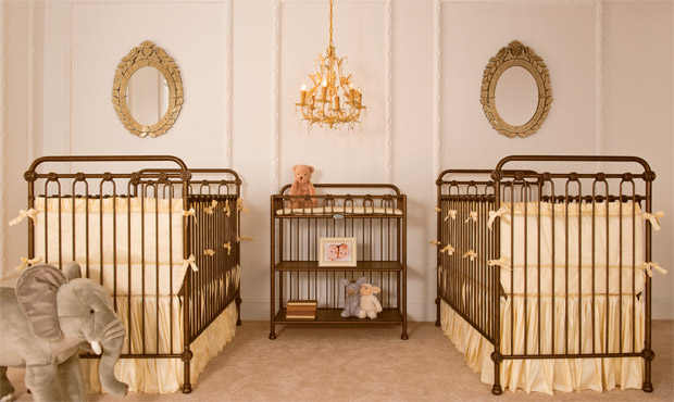 Paired gold iron cribs dressed in warm yellow makes this upscale twin nursery stylish and graceful.