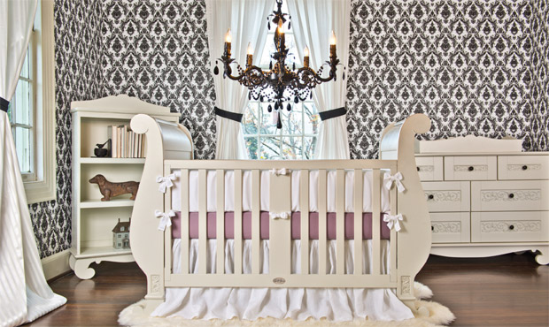 Oversized, carved white furniture sing against a backdrop of black and white damask walls.